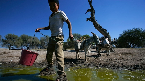 Local people collecting water from a muddy waterhole in Mexico