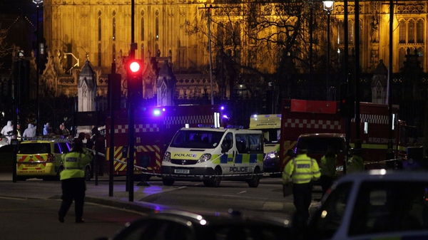 Police stand on duty as forensics officers work outside the entrance of the Houses of Parliament in Westminster