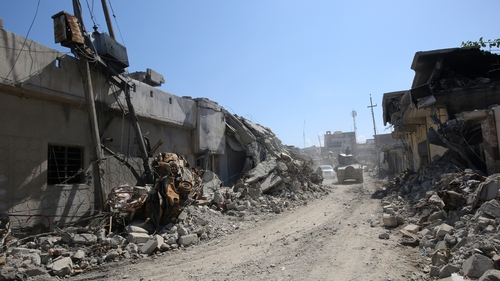 An Iraqi forces' vehicle drives past destroyed buildings in Mosul's al-Jadida area today
