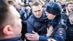 Russian opposition leader Alexei Navalny (C) was detained by Russian police officers during the opposition rally in central Moscow