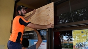 Workmen put up plywood panels in preparation for Cyclone Debbie