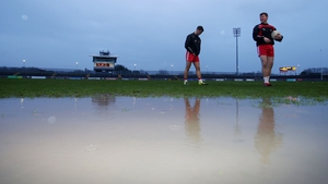 Players walk around one of the large puddles at Healy Park after the game was called off.