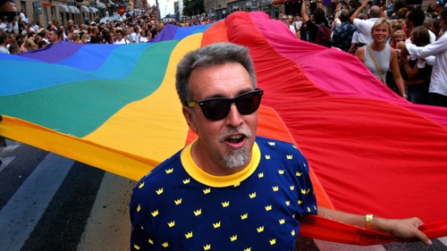 Gilbert Baker with the iconic rainbow coloured flag on a march in 2003