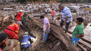 Rescuers search for people among the rubble left by mudslides following heavy rains in Mocoa