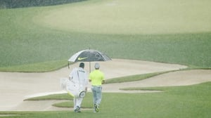 Rory McIlroy is sheltered from the rain at the 2015 US Masters