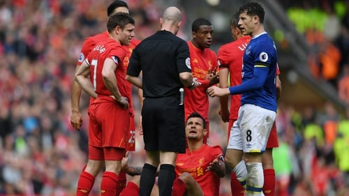 Lovren lies on the ground and appeals to referee Anthony Taylor after a foul by Barkley (r)
