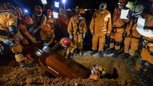 Colombian civil defence workers bury a coworker who died during the rescue effort