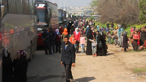 At least 100 killed after bomb hits bus convoy in Syria