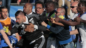 Security staff holds Lyon's goalkeeper Anthony Lopes (C) during scuffles at half-time