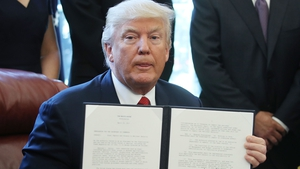 US President Donald Trump holds up his executive memorandum on the investigation of steel imports