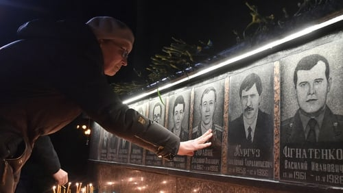 A woman touches a portrait during a memorial ceremony at the monument to Chernobyl victims in Slavutich