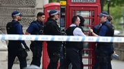 Armed police lead a man away following the incident in Whitehall