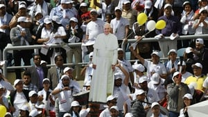 Worshippers hold a cardboard cut-out of Pope Francis before the start of a mass at a stadium in Cairo