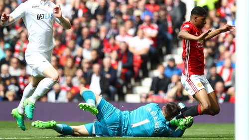 Manchester United's Marcus Rashford falls as Swansea keeper Lukasz Fabianski dives near his feet