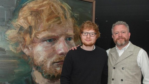 Ed Sheeran posing with his giant portrait alongside artist Colin Davidson