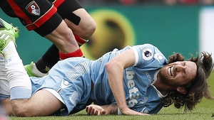 Joe Allen winces in pain after a tackle from Harry Arter
