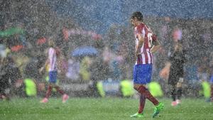 Heavy rain falls on Atletico Madrid defender Stefan Savic