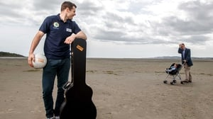 Just Kevin McManamon on the beach with a guitar and a football