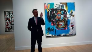 A Sotheby's official speaks about the painting by Jean-Michel Basquiat during a media preview earlier this month