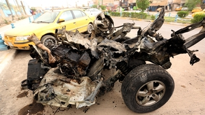 A wrecked car at the site of a suicide car bomb attack that targeted a police checkpoint in Baghdad