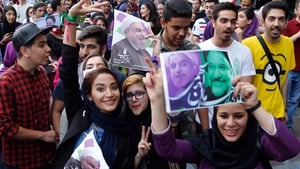 Supporters of Iranian president Hassan Rouhani hold pictures of him as they celebrate his victory on the streets of Tehran
