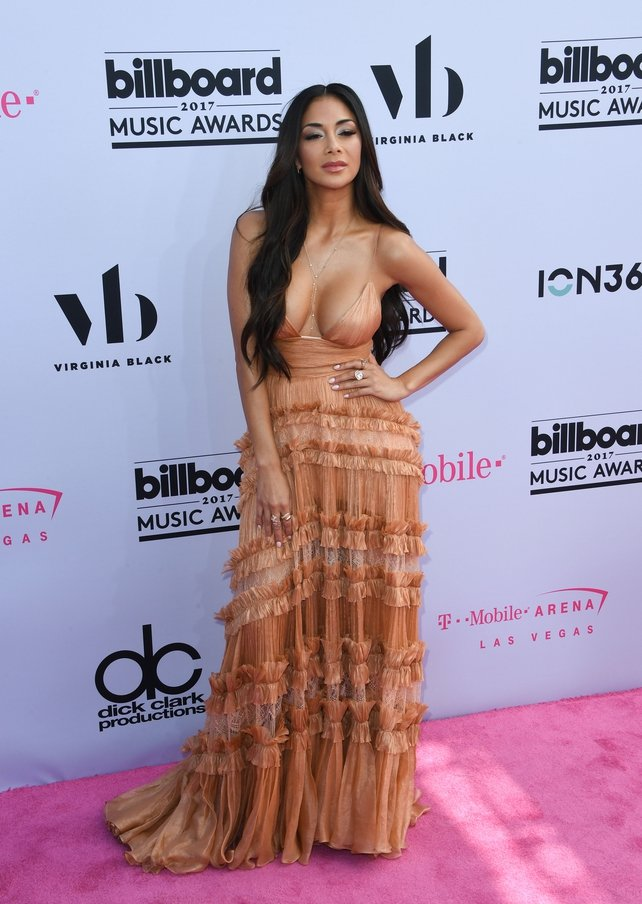 Singer Nicole Scherzinger wore a plunging dress with peach tones and a stunning collection of rings.