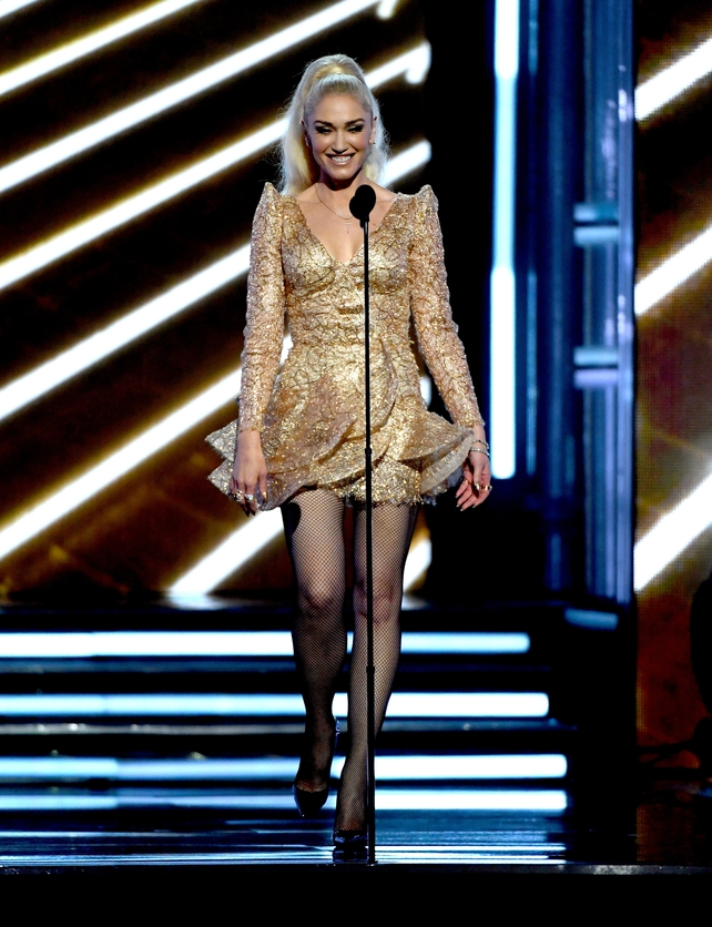 Singer Gwen Stefani rocked a gold mini dress with fishnet stockings, a high pony and exaggerated shoulder detail.