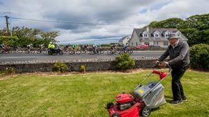 Thady Kilgannon mows his lawn in Dromore West, Co Sligo as the field passes by