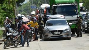 Philippine policemen check the belongings of residents fleeing Marawi