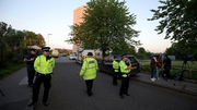 Police stand outside a block of flats in Blackley, Greater Manchester