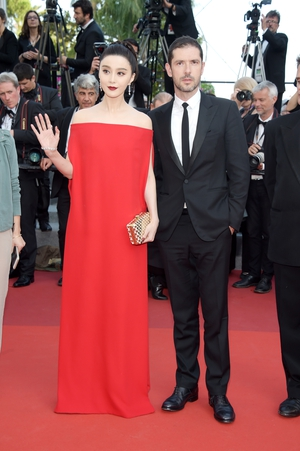 Day Eight - Wednesday May 24: Member of jury Fan Bingbing has so much allure in this Valentino Bardot dress alongside French actor Melvil Poupaud.