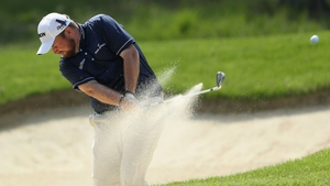 Shane Lowry plays from the bunker on the ninth hole