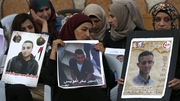 Palestinain women hold portraits of relatives imprisoned in Israeli jails during a protest in front of the Red Cross offices in east Jerusalem