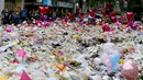 People lay flowers at a memorial for the victims at St Ann's Square, near Manchester Arena