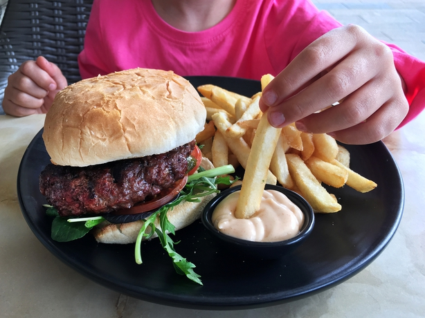 child eating burger and chips
