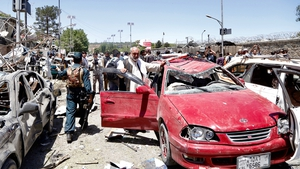 Afghan security officials inspect the scene of the suicide bomb attack in Kabul