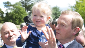 Taoiseach Enda Kenny and little pal wave to crowds at Bloom