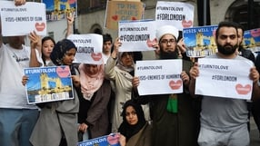 Members of London's Muslim community hold signs of condolence and support near the site of the attack at Borough Market