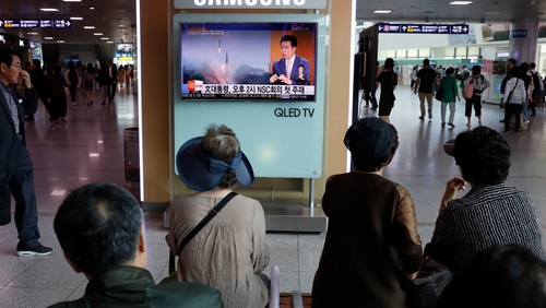 South Koreans watch a television broadcasting a news report on North Korea's recent missile launch