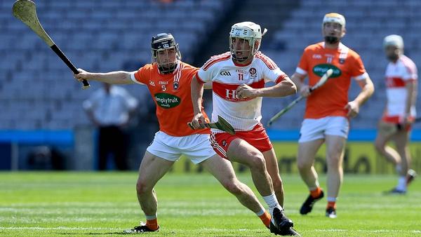 Armagh's John Corvan tries to dispossess Derry forward Mehaul McGrath