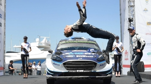 Estonian driver Ott Tanak (R) looks at his co-driver Martin Jarveoia of Ford Fiesta RS WRC celebrating in style