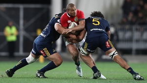 Jonathan Joseph of the Lions is tackled by Aki Seiuli (L) and Jack Hemopo (R)