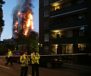 Police officers in position at the edge of a cordoned-off area around Grenfell Tower