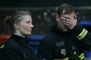Fire fighters react as the Grenfell tower burns on