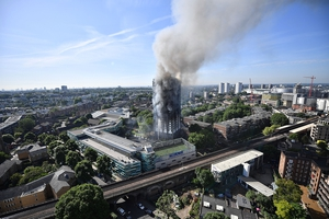 Smoke rises from the tower as the fire continues to burn