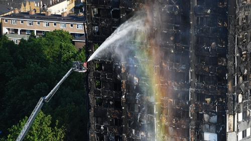 Firefighters spray water on the smouldering tower earlier this evening