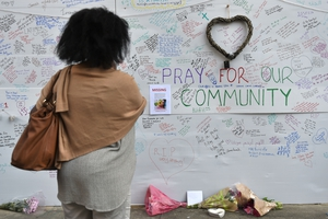 A woman views a tribute wall near the Grenfell Tower