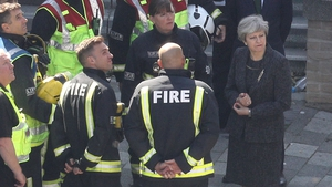 Theresa May speaks to fire fighters while visiting the site of the Grenfell Tower fire