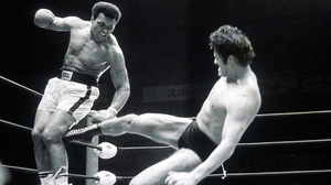 Muhammad Ali fends off a kick from wrestler Anthony Inoki during an exhibition fight in Tokyo, Japan in 1976