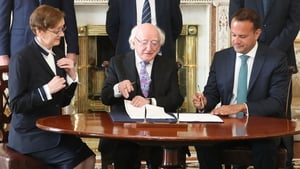 President Michael D Higgins and Taoiseach Leo Varadkar sign the documents to seal Máire Whelan's appointment to the Court of Appeal